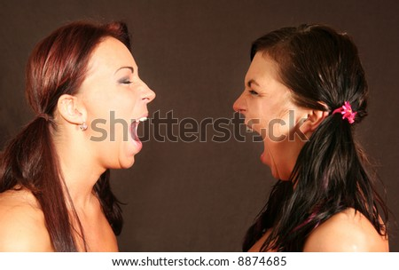 Studio portrait of two caucasian white young women screaming. Fighting/arguing.