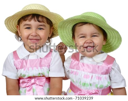 studio portrait of two sisters in spring dresses sitting side by side, Hispanic, ages one and three years, isolated on pure white background - stock photo