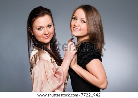 Studio portrait of two young beautiful sisters holding hands and smiling - stock photo