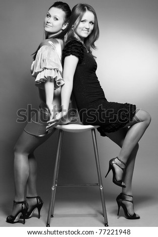 Studio portrait of two young beautiful sisters holding hands and smiling while sitting on a stool, black and white - stock photo