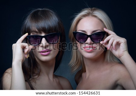 Studio portrait of two young beautiful women models wearing sun glasses, smiling and looking at camera. Black background
