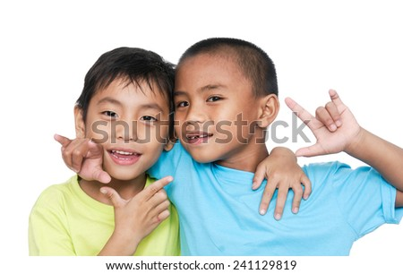 Studio portrait of two young brothers hugging and smiling - stock photo