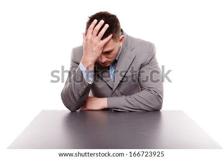 Studio portrait of unhappy businessman sitting at desk with hand on the head, isolated over white background - stock photo