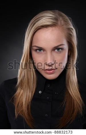 Studio portrait of unsmiling, blonde teenager in black, black background .? - stock photo