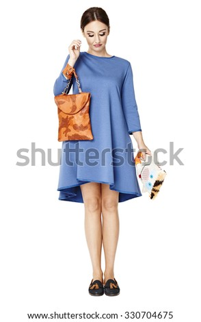 Studio portrait of woman looks down. She holds a bag and mascot. - stock photo