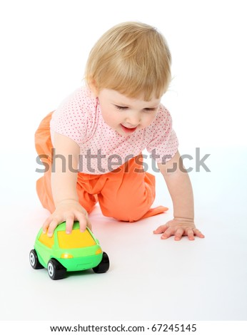Studio portrait of 1 year old baby playing with a toy car on the white background
