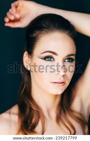 Studio Portrait of Young Attractive Woman close up with beautiful blue eyes looking slightly up away from camera arm over head mouth slightly open - stock photo