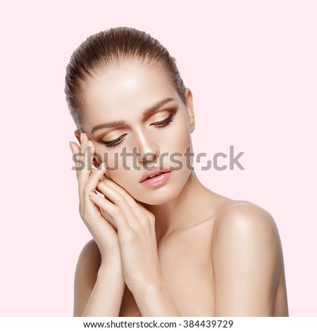 Studio portrait of young beautiful model with professional makeup on pink background. Perfect fresh clean skin. Deep blue eyes. Brunette hair. Hands touching her face. Not isolated - stock photo