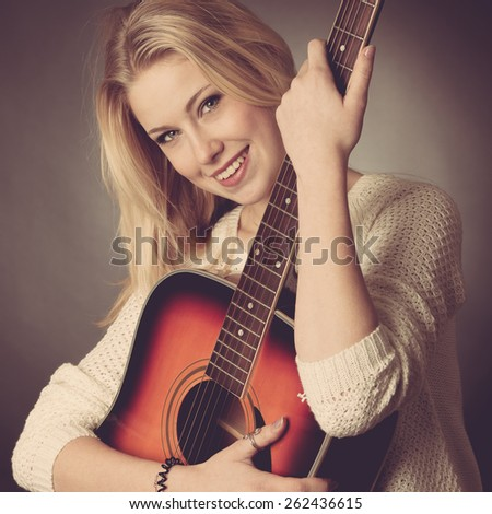 studio Portrait of young blonde guitar player - stock photo