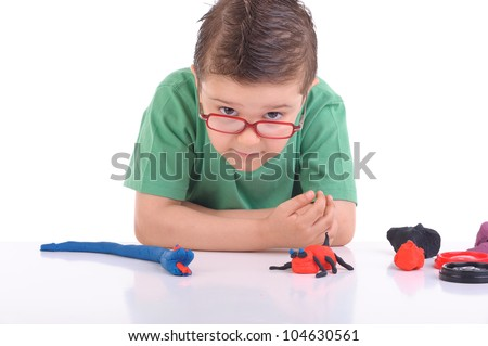 studio portrait of young boy  playing with modeling clay or play doh
