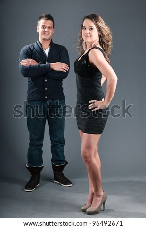 Studio portrait of young couple isolated on grey background