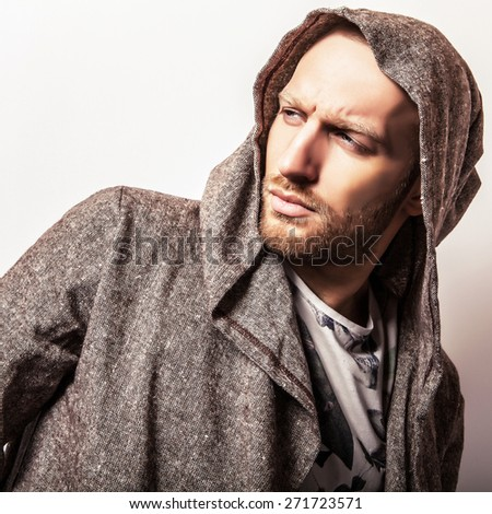 Studio portrait of young handsome man in casual cape with a hood. Close-up photo.