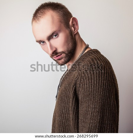 Studio portrait of young handsome man in casual knitted sweater. Close-up photo.  - stock photo