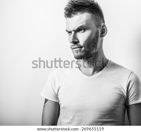Studio portrait of young handsome man in casual white t-shirt. Black-white close-up photo. - stock photo