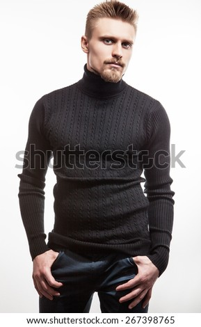 Studio portrait of young handsome man in knitted sweater. Close-up photo.