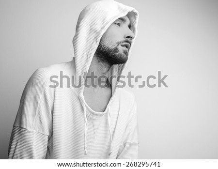 Studio portrait of young handsome man in white sweater with hood. Black-white photo. - stock photo