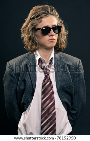 Studio portrait of young hip cool business man with long blond hair and black sunglasses on black background.