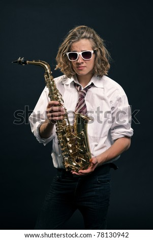 Studio portrait of young hip cool man with saxophone and white sunglasses on black background.