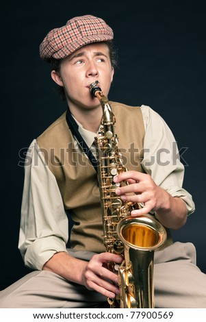 Studio portrait of young man in 20s style playing saxophone. Isolated on black background.