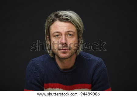 Studio portrait of young man long blond hair wearing woolen sweater isolated on black background.