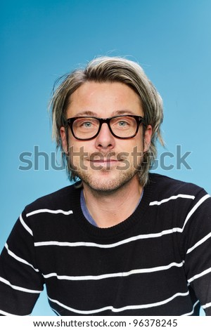 Studio portrait of young man with long blond hair wearing glasses and black sweater. Isolated on light blue background. - stock photo