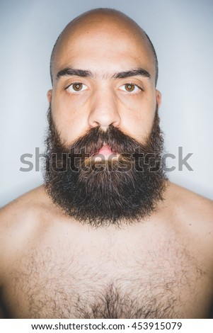 Studio portrait of young mid adult bearded man looking at camera - beard care, wellness concept - stock photo