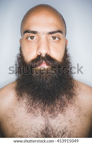 Studio portrait of young mid adult long beard man looking at camera - beard care, wellness concept - stock photo