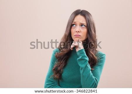 Studio portrait of young pensive woman - stock photo