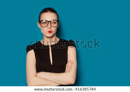 Studio Portrait of young pretty thoughtful criticizing female. Colorful blue background, isolated
