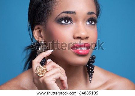 Studio portrait of young sensual happy woman, isolated on blue - stock photo