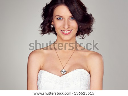 studio portrait of young smiley bride - stock photo