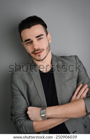 studio portrait of young trendy man posing in front of a gray wall