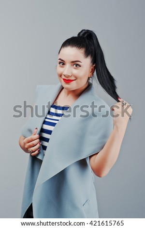 Studio portrait of young woman at coat with red lips - stock photo