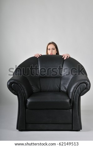 Studio portrait of young woman hidden behind big black armchair - face with hands visible