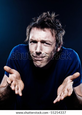 studio portrait on black background of a funny expressive caucasian man frowning anxious - stock photo