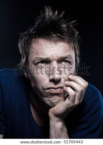 studio portrait on black background of a funny expressive caucasian man frowning sad - stock photo