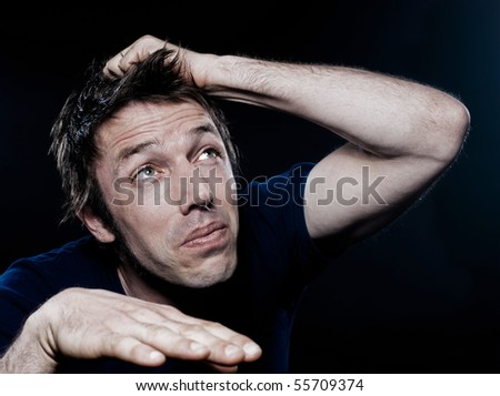 studio portrait on black background of a funny expressive caucasian man looking up scare