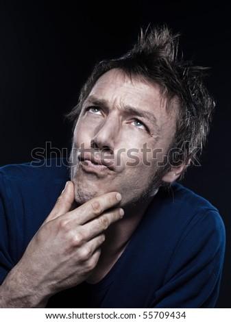studio portrait on black background of a funny expressive caucasian man puckering pensive - stock photo