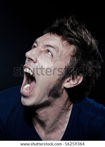 studio portrait on black background of a funny expressive caucasian man screamin - stock photo