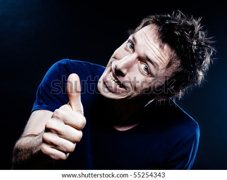 studio portrait on black background of a funny expressive caucasian man thumb up cheerful - stock photo