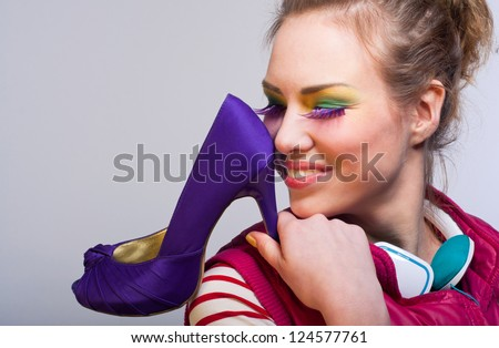 Studio portrait on gray of young beautiful fashion girl wearing colorful makeup with purple long eyelashes, green earphones, pink vest, holding violet high heel shoe and looking with toothy smile - stock photo