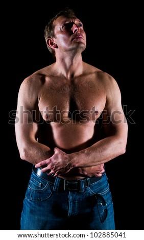 Studio portrait on muscular man, black background. - stock photo