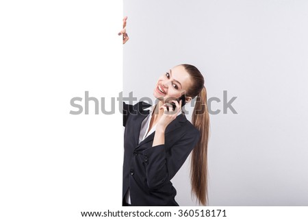 studio portrait on white background successful woman in a business suit is talking on the phone next to the board for advertising - stock photo