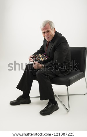 Studio portrait over white of an old man in a suit, sitting in a chair and protecting a large box of chocolates from anyone who may wish to share - stock photo