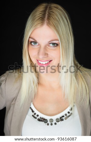 Studio portrait pretty young woman with blond hair wearing white shirt and light brown jacket. Isolated on black background.