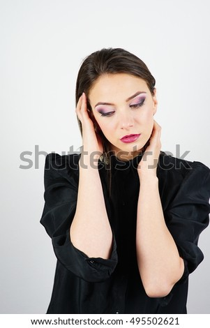 Studio portrait shot of a young brunette Caucasian woman in black shirt isolated on white background.