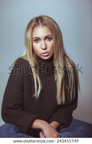Studio portrait young woman sitting on floor. Gorgeous woman in casual outfit. - stock photo