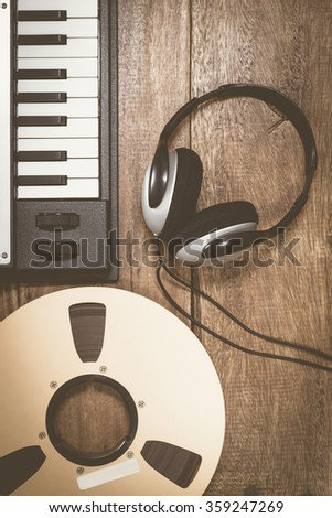 studio reel tape, headphone & synthesizer keyboard on wooden table + vintage filter for music background - stock photo