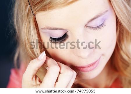 Studio series of doing fashion makeup: applying false eyelashes - stock photo