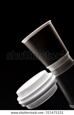Studio shoot of black Coffee to go cup on black background with reflection on glass